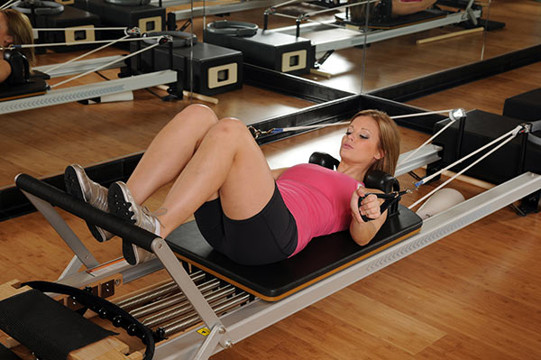 woman performing Pilates exercise